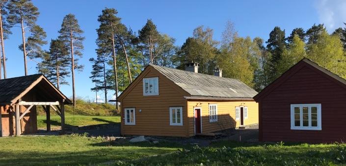 Det historiske tunet på Lyngheim med Lemstova, skykkjo; og rosemålarverkstaden som er under arbeid. (Foto: Tone Brodal Mongstad, mai 2020)